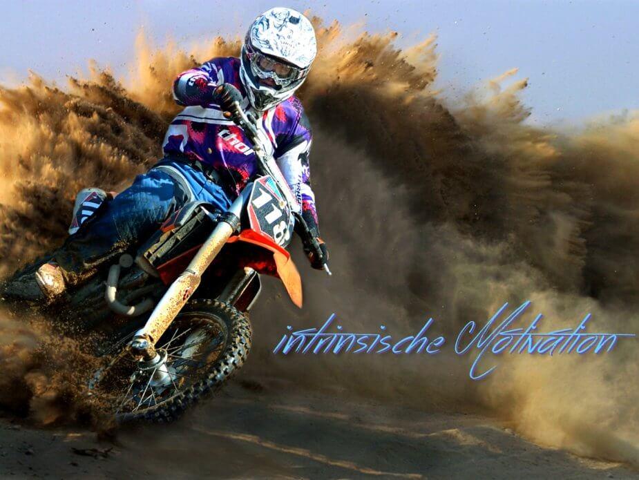 Intrinsische Motivation verbildlicht duch einen Moto-Cross-Fahrer im aufwirbelnden Staub